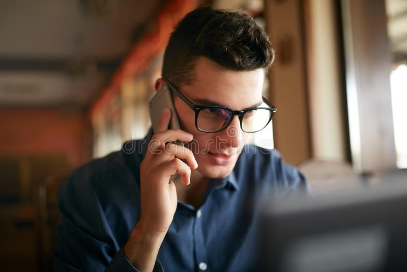 Ung freelancer som arbetar med bärbara datorn och i regeringsställning talar på mobiltelefonen med klienten Stilig caucasian affä arkivfoton