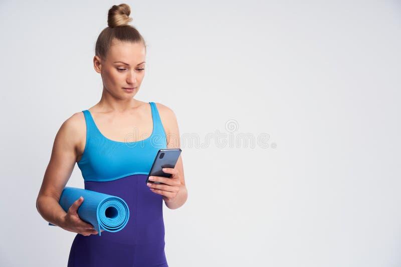 Ung friidrottskvinna med mobiltelefon och en Mat för gymnastik i hennes händer arkivfoton