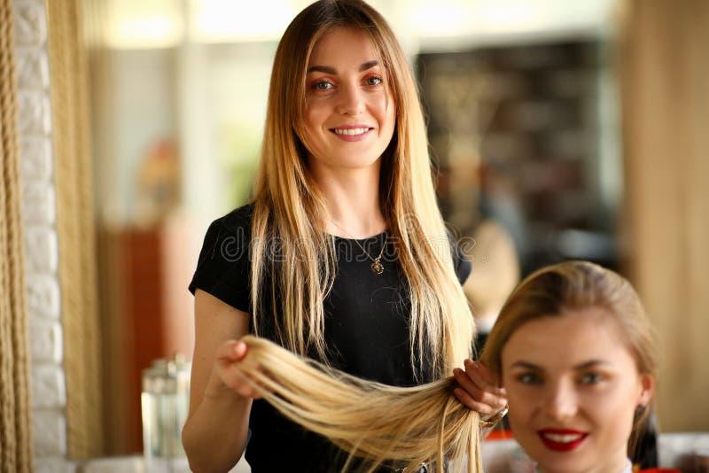 Ung frisör Holding Hair av den kvinnliga klienten arkivbilder