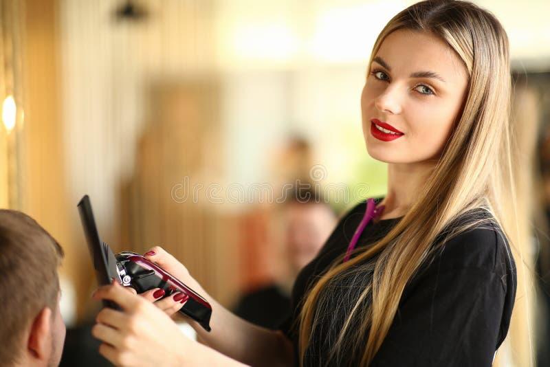 Ung frisör Using Electric Razor och hårkam royaltyfria foton