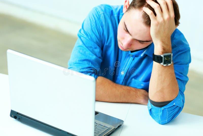 Ung fundersam affärsman i blått skjortasammanträde på tabellen med bärbara datorn royaltyfria foton