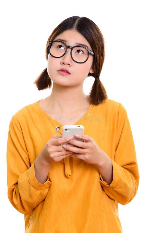 Ung fundersam asiatisk kvinnainnehavmobiltelefon fotografering för bildbyråer