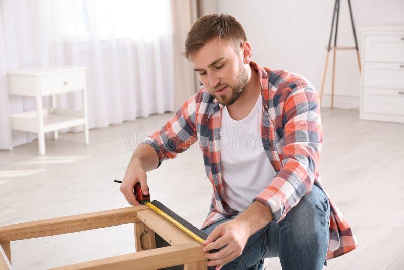 Ung funktionsduglig man som hemma använder måttbandet arkivbild
