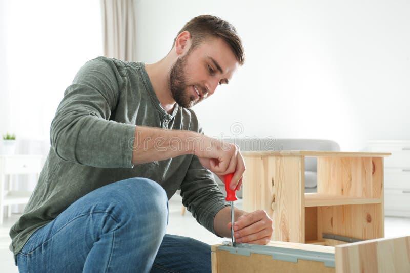 Ung funktionsduglig man som reparerar enheten arkivfoto