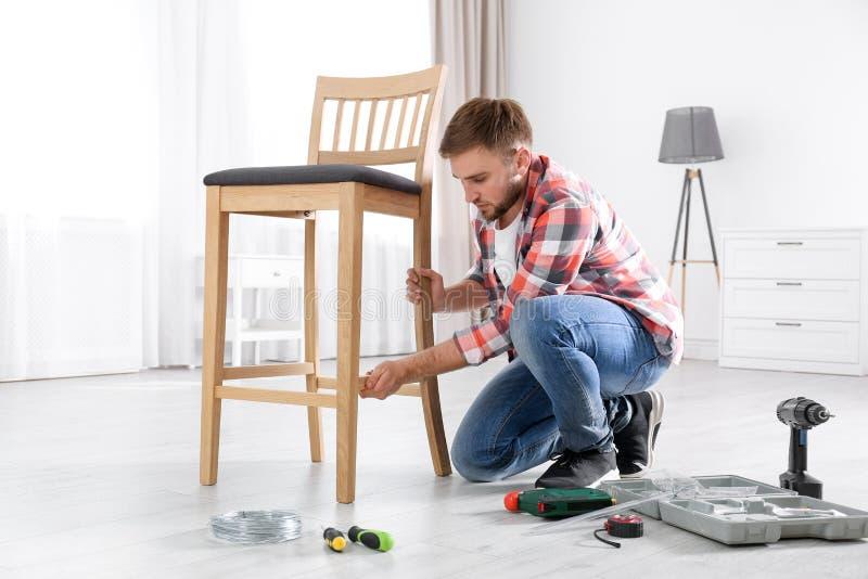 Ung funktionsduglig man som reparerar stol royaltyfri fotografi