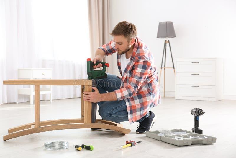 Ung funktionsduglig man som reparerar stol royaltyfria foton