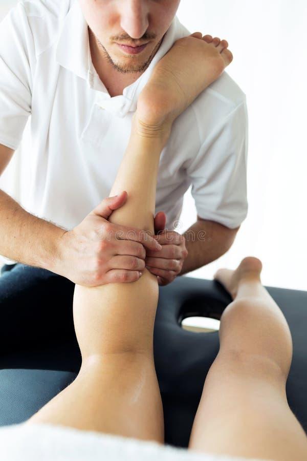 Ung fysioterapeut som g?r en benbehandling till patienten i ett sjukgymnastikrum royaltyfri foto