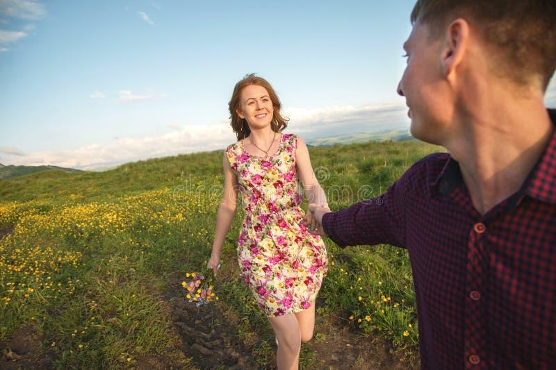 Ung gift par Grabben leder en lockig flicka med en bukett av blommor arkivfoto