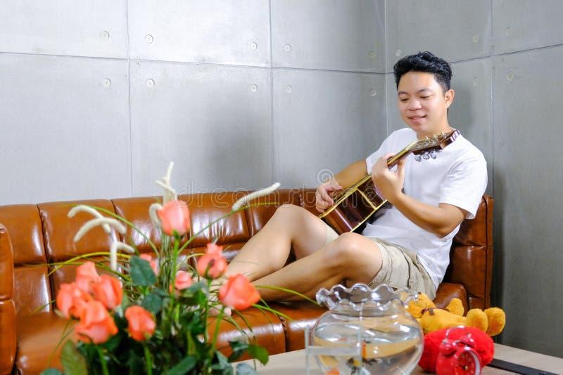 Ung gitarristhipster hemma med gitarren på den bruna soffan arkivbilder