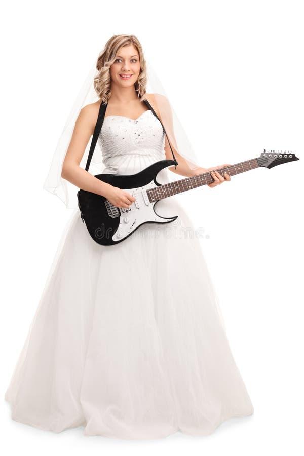 Ung glad brud som spelar den elektriska gitarren arkivbild