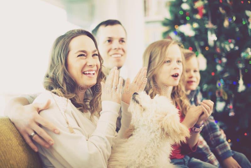 Ung gladlynt familj som tycker om julhemafton royaltyfria foton