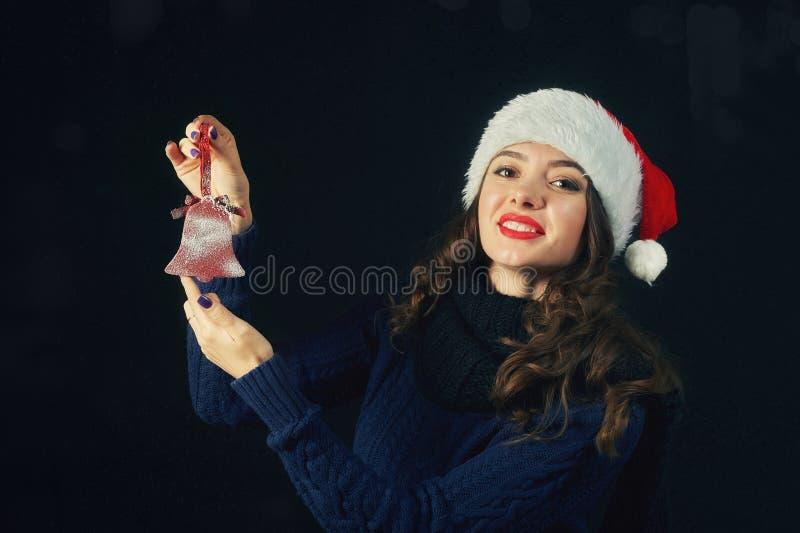 Ung gladlynt flicka i jultomtenhatt på mörk bakgrund royaltyfri fotografi