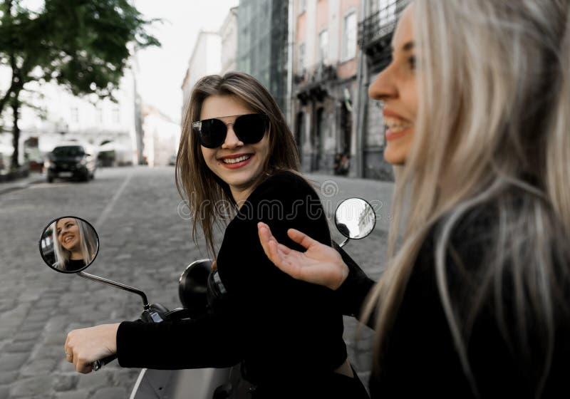 Ung gladlynt flicka med sparkcykeln i europeisk stad royaltyfri fotografi