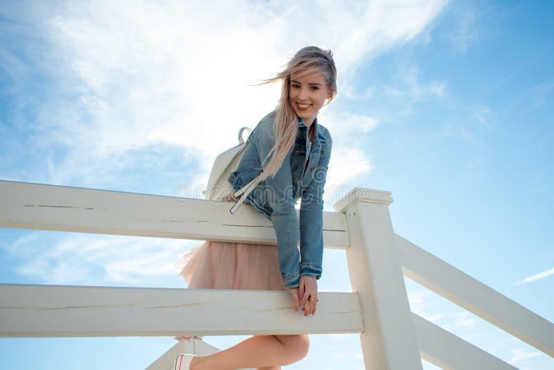 Ung gladlynt flicka på kusten le kvinnabarn för blondin Moderiktig beige kjol arkivfoton