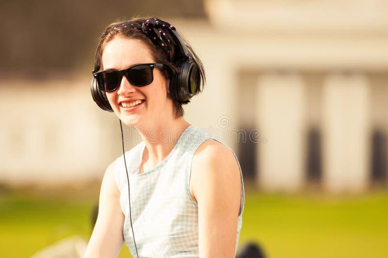 Ung gladlynt hipsterkvinna som lyssnar till musik i parkera royaltyfri fotografi