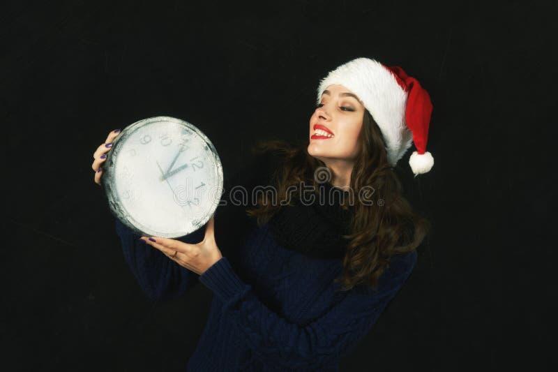 Ung gladlynt kvinna i jultomten hatt och klockor arkivfoto