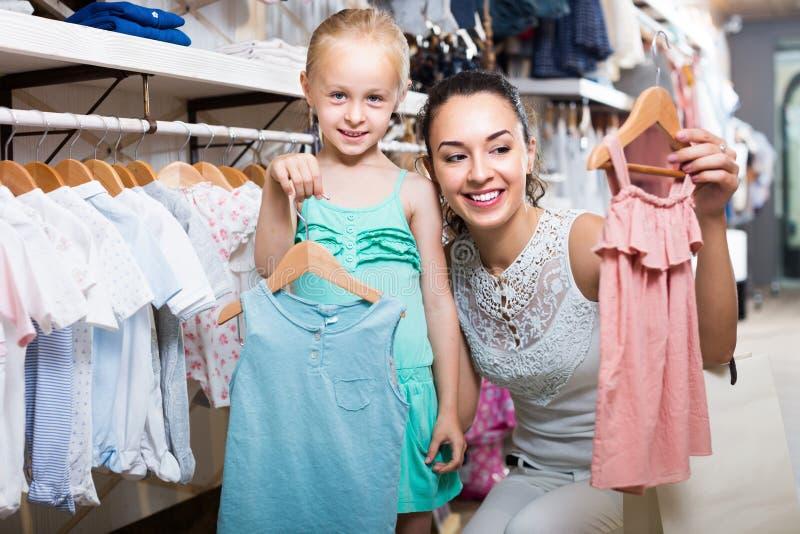 Ung gladlynt kvinna med den lilla flickan som väljer kläder royaltyfri fotografi