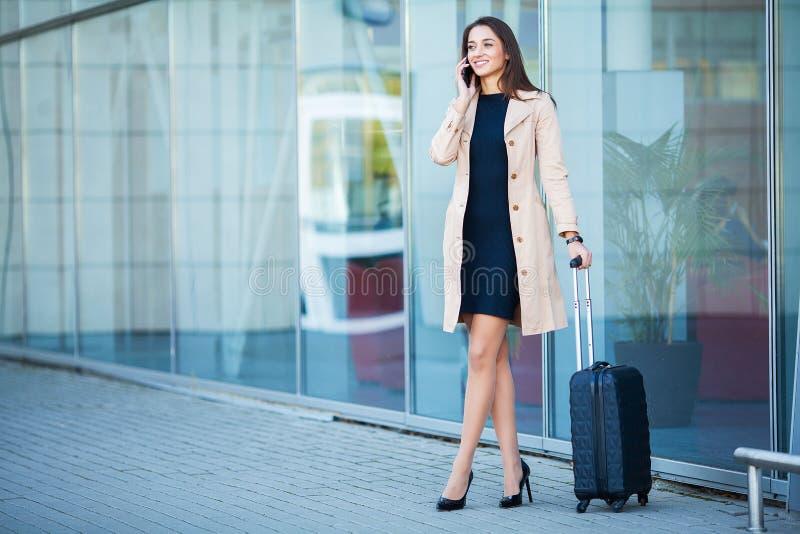 Ung gladlynt kvinna med en resväska Begreppet av loppet, wor royaltyfria foton