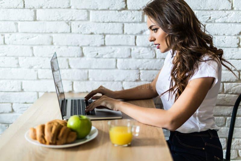 Ung gladlynt kvinna som använder på bärbar datordatoren och äter frukter i köket i morgonen arkivfoto