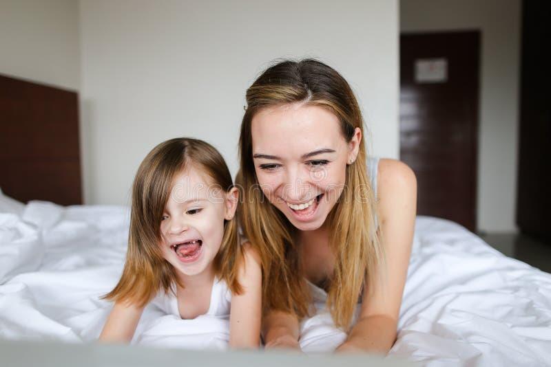 Ung gladlynt kvinna som ligger i säng med den lilla dottern i morgon arkivfoto