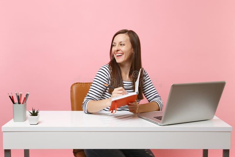 Ung gladlynt kvinna som ser skriva åt sidan anmärkningar på anteckningsboksammanträde och arbete på det vita skrivbordet med den  royaltyfri fotografi
