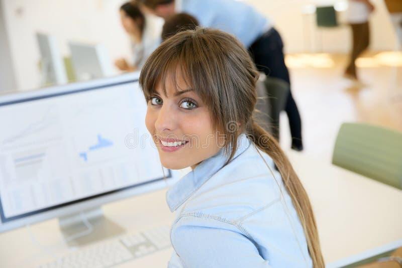 Ung gladlynt kvinnakontorsarbetare på datoren arkivfoto