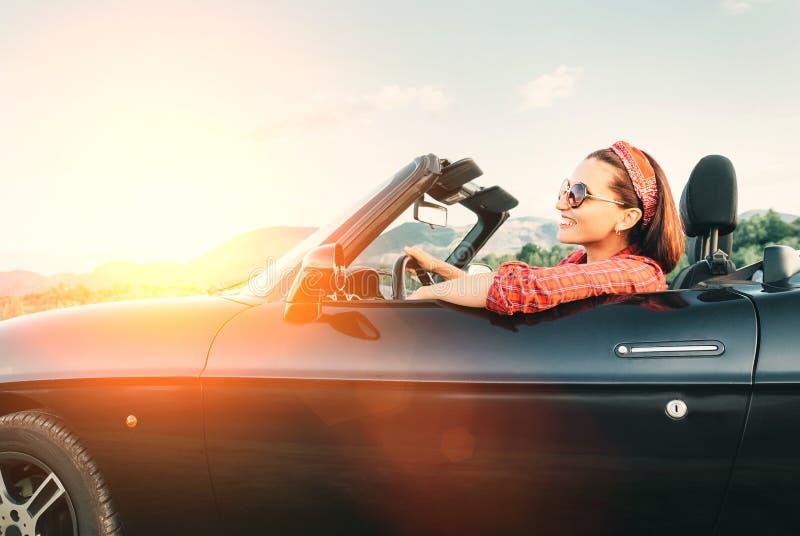 Ung gladlynt le kvinnlig körande konvertibel bil på tid för solig dag arkivfoton