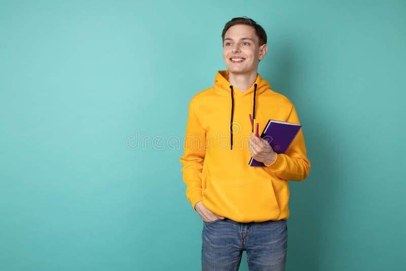 Ung gladlynt man som bär den gula hoodien och att rymma den purpurfärgade anteckningsboken och pennan Inspiration som ska skapas arkivfoton