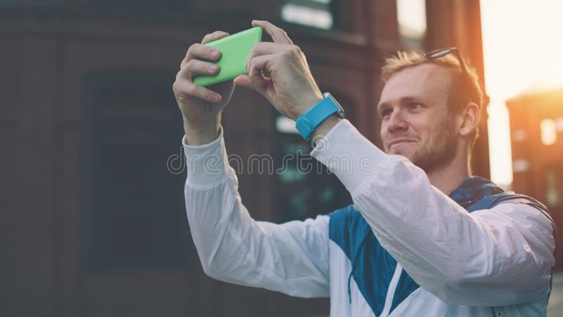 Ung gladlynt man som tar fotoet med hans smartphone på gatan royaltyfria foton