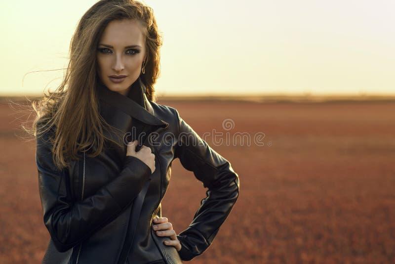 Ung glam modell med vinden i hennes långa hår som bär svart stilfullt anseende för läderomslag i det öde fältet på solnedgången royaltyfri foto