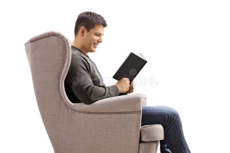 Ung grabb i en fåtölj som läser en bok arkivfoton