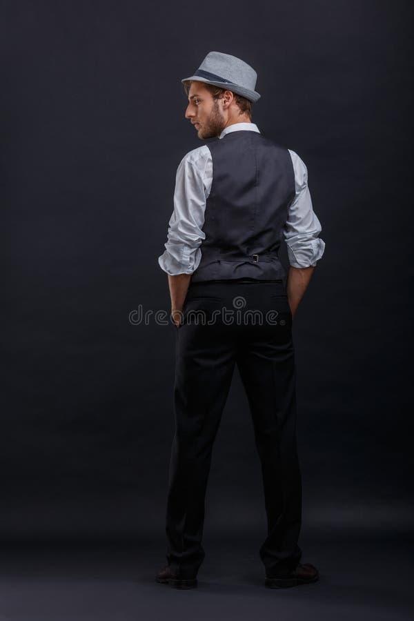 Ung grabb i en retro dräkt med en väst och en hatt, ställningar med hans baksida och håll hans händer i facken royaltyfri fotografi
