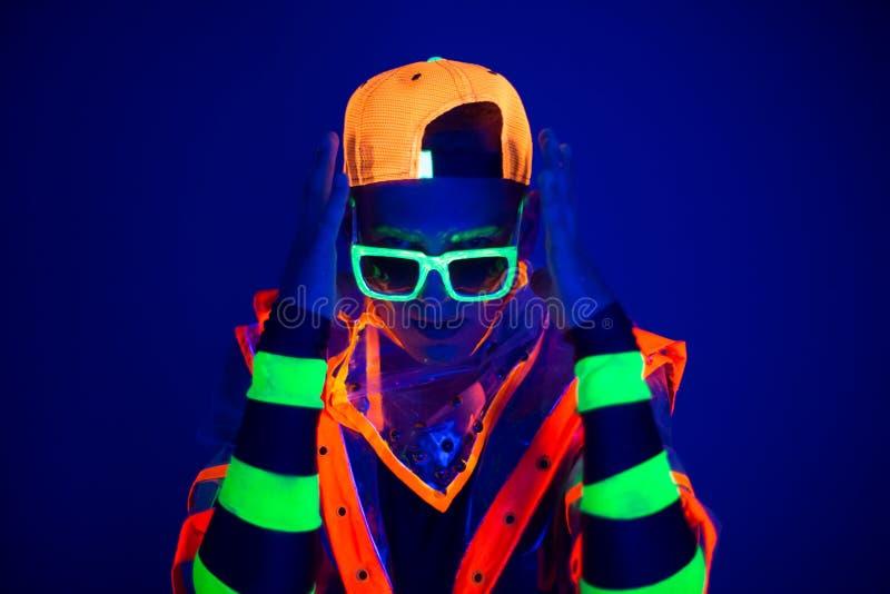 Ung grabb i idérik dräkt med neonglöd arkivfoton