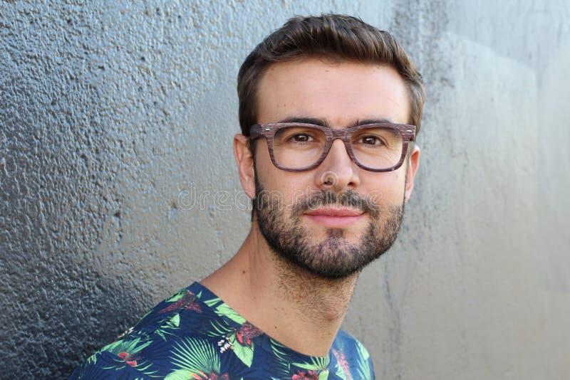 Ung grabb med ett skägg och mustasch med exponeringsglas i en blommig eller blom- skjorta som poserar på gatan, modeman, stil, ta arkivbilder