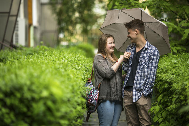 Ung grabb och flicka som talar under ett paraply Förälskelse fotografering för bildbyråer