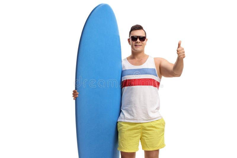 Ung grabb som rymmer en surfingbräda och gör en tumme upp gest royaltyfri fotografi