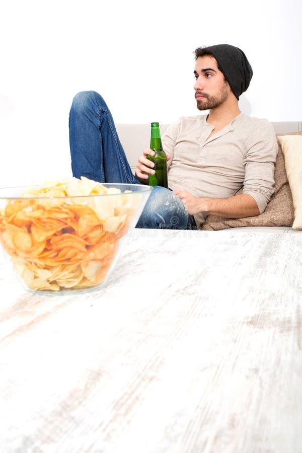 Ung grabb som tycker om öl och chiper i vardagsrummet royaltyfria foton