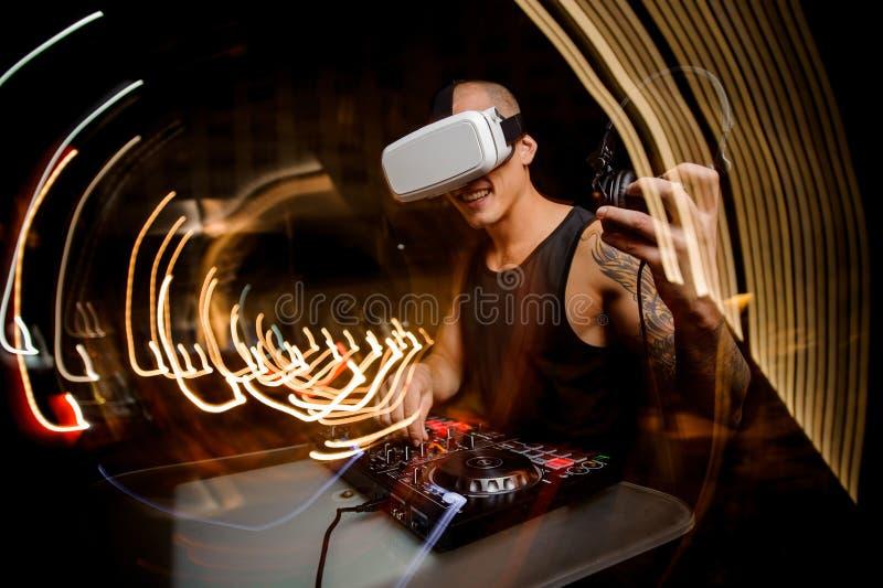 Ung grabbdiscjockey i exponeringsglas av virtuell verklighet mot bakgrunden av nattstaden arkivfoto