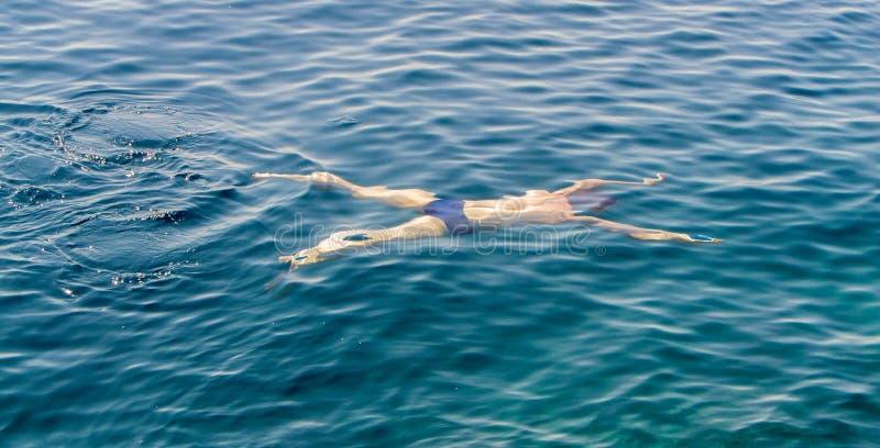 Ung grabbsimning i havet fotografering för bildbyråer