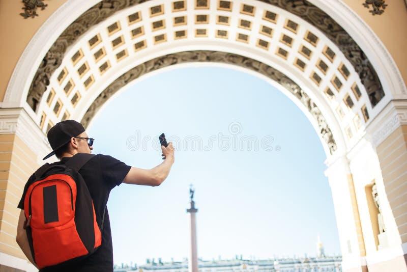 Ung grabbturist med ryggsäcken som tar det mobila fotoet i slottfyrkanten i St Petersburg royaltyfri fotografi