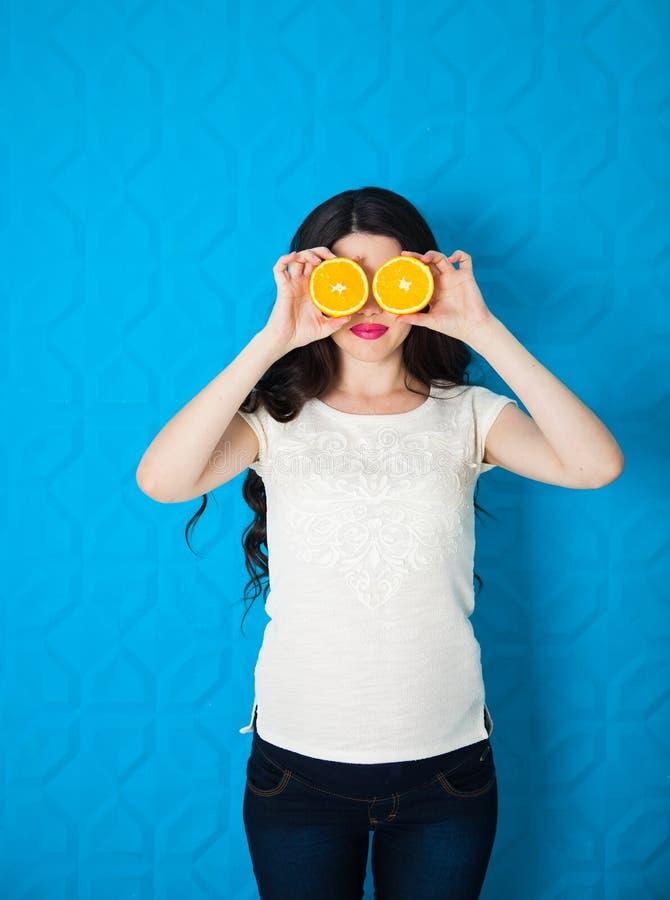 Ung gravid kvinna för härlig närbild med apelsiner på blåttbac arkivfoto