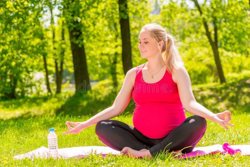 Ung gravid kvinna i en lotusblommaposition som gör yoga royaltyfria bilder