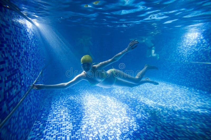 Ung gravid kvinna som är undervattens- i simbassäng arkivbilder