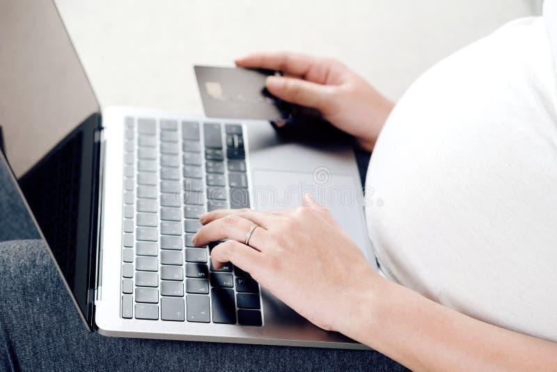 Ung gravid kvinna som använder bärbara datorn för online-shopping och holdin fotografering för bildbyråer