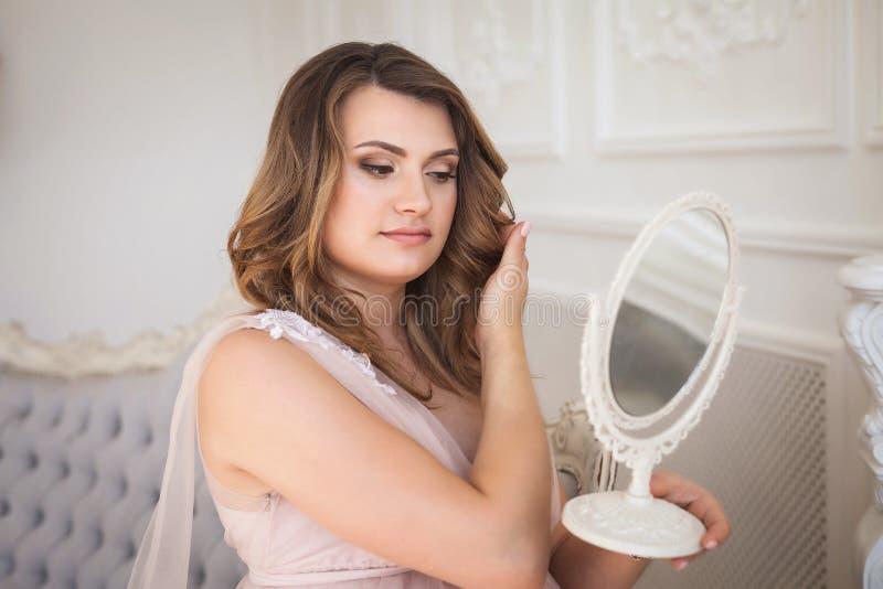 Ung gravid kvinna som beundrar reflexionen i spegeln på soffan i studio royaltyfri bild