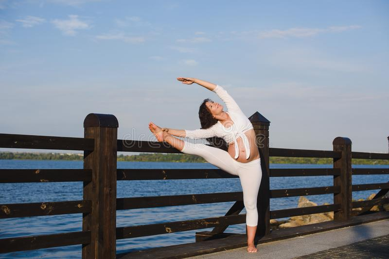 Ung gravid kvinna som gör yoga vid floden royaltyfri fotografi