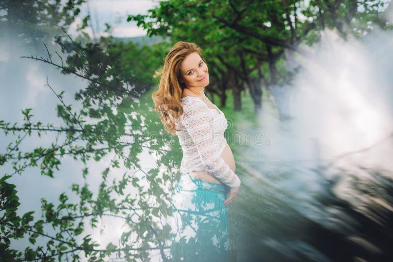 Ung gravid kvinna som ler i körsbärsröda trän royaltyfri fotografi