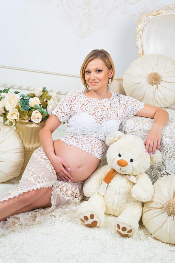 Ung gravid kvinna som sitter nära den vita soffan med nallebjörnen royaltyfria bilder