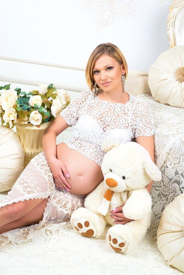 Ung gravid kvinna som sitter nära den vita soffan med nallebjörnen arkivbilder