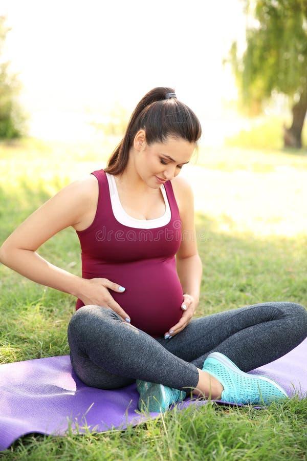 Ung gravid kvinna som sitter på matt det fria för yoga royaltyfri fotografi